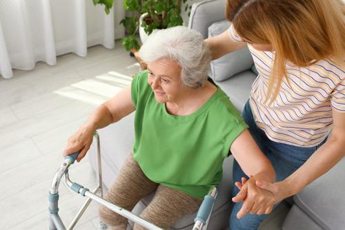 Pflegerin hilft Seniorin am Rollator aufzustehen