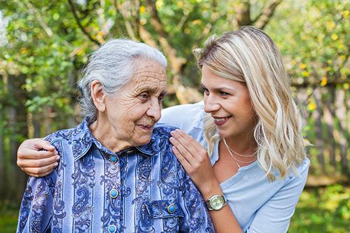JUnge Frau umarmt Seniorin