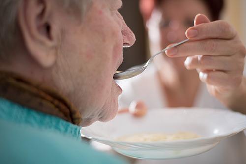 Pflegerin füttert Seniorin