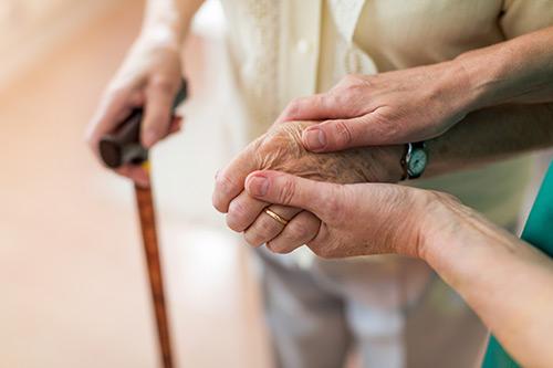 Seniorin geht mit Stock