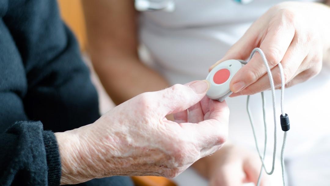 Pflegerin reicht Senioren einen Hausnotruf
