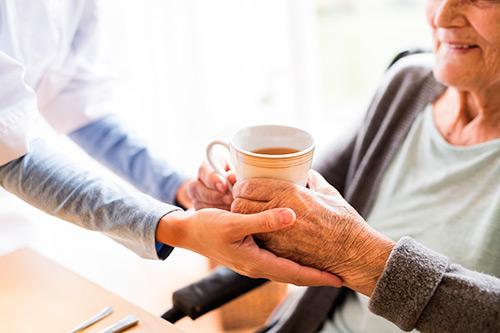 Pflegerin reicht Seniorin eine Tasse Kaffee