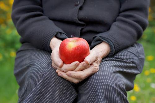 Seniorin mit Apfel in Händen
